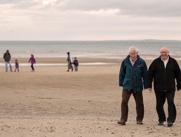 Image of a man with dementia and a carer out at the beach. LifeCare Edinburgh will find a way to reach them and bring extra years of zest.
