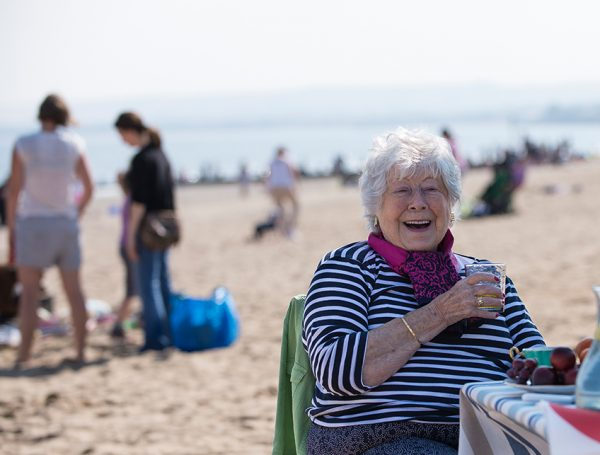 LifeCare Edinburgh enriching the lives of the elderly. A lady enjoying a day out at the beach.