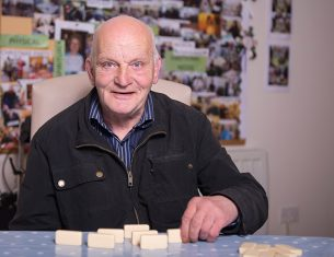 Elderly man playing dominoes at LifeCare Edinburgh